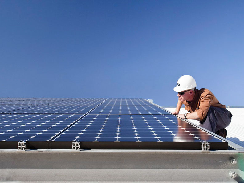 Kneeling man inspecting a SunPower solar panel system